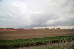Weitwinkelansicht des Feldes, die nach Ernte von Tulpenbirnen mit dunklen Wolken gepflogen worden sind lizenzfreie stockfotos