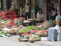 Weitwinkelfoto von vietnamesischen Weidenkörben voll von Wurzeln, von Knoblauch, von Frucht, von Gemüse und von heißen roten Pfef Stockfoto