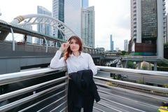 Weitwinkelschuß der überzeugten jungen asiatischen Geschäftsfrau, die denkt, um am städtischen Stadthintergrund nachzuschicken lizenzfreie stockbilder
