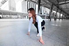 Weitwinkelschuß der attraktiven jungen Asiatin in der Anfangsposition bereit, am städtischen Stadthintergrund zu laufen Wettbewer Stockfotos