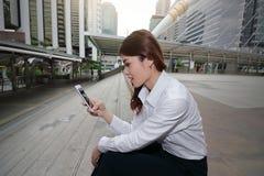 Weitwinkelschuß der attraktiven jungen asiatischen Geschäftsfrau, die intelligentes Mobiltelefon in ihren Händen äußerem Büro mit stockfoto