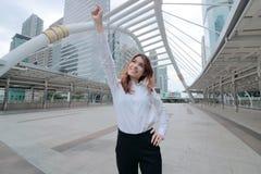 Weitwinkelschuß der erfolgreichen jungen asiatischen Geschäftsfrau, die ihre Hand anhebt und am städtischen Gebäudehintergrund lä Stockfotografie