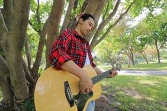 Weitwinkelschuß des hübschen jungen Mannes, der Musik auf Akustikgitarre in einem schönen Naturhintergrund spielt Lizenzfreie Stockfotos