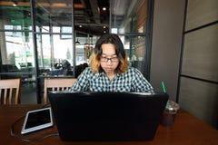 Weitwinkelschuß des jungen asiatischen Mannes, der mit Laptop für seinen Job an Arbeitsplatz des Büros arbeitet lizenzfreie stockbilder