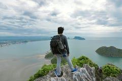 Weitwinkelschuß des jungen asiatischen Mannes des Hippies mit dem Rucksack, der auf dem Stein auf dem Berg steht und in den Absta Lizenzfreies Stockbild