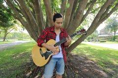 Weitwinkelschuß des jungen Hippie-Mannes, der Musik auf Akustikgitarre in einem schönen Naturhintergrund spielt Stockfoto