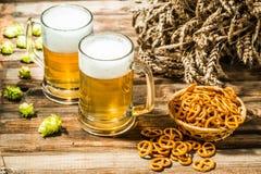 Weizenährchen mit zwei Bechern Bier mit Hopfen, Brezeln auf Holztisch Stockfotografie
