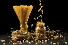 Weizenbündel, -makkaroni und -teigwaren im Glas, auf schwarzem Hintergrund Kornblumenstrauß, goldene Ährchen auf dunklem Holztisc Lizenzfreies Stockfoto
