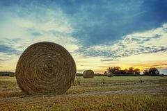 Weizenfeld nach Ernte mit runden Strohballen in der Wiese auf Ackerland mit blauem bewölktem Himmel Lizenzfreies Stockfoto