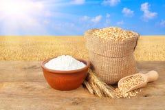 Weizenkörner und -mehl auf Naturhintergrund Stockbild