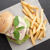 Weizenrindfleisch-Sandwichhamburger, gebratene Kartoffeln, Ketschup diente FO Lizenzfreie Stockbilder