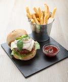 Weizenrindfleisch-Sandwichhamburger, gebratene Kartoffeln, Ketschup diente FO Stockbilder