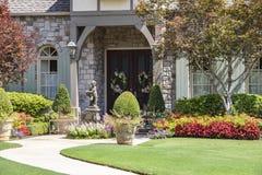 Wejście ekskluzywny skała dom z piękny kształtować teren, statua, wianki i ławki obok ganku frontowego fotografia royalty free