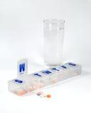 Wekelijkse pillendoos met glas water stock foto