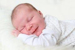 3-weken pasgeboren meisjesglimlachen tijdens een slaap Stock Fotografie