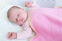 2-weken pasgeboren meisjesslaap in reisvoederbak Stock Foto
