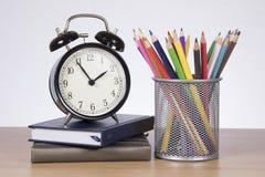 Wekker, boeken en school stationaire levering stock fotografie