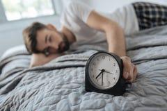 Wekker die zich op het bed bevinden royalty-vrije stock foto's