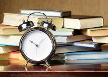Wekker en boeken. Onderwijsconcept Stock Fotografie