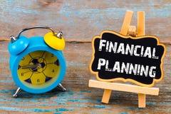 Wekker en een bord met tekst - financiële planningб, Royalty-vrije Stock Foto