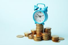 Wekker en gouden geldmuntstukken, kapitalisatie De tijd is geldconcept, betaling stock fotografie