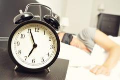 Wekker en jonge mensenslaap in bed met een slaapmasker Stock Afbeeldingen