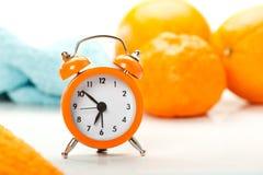 Wekker en sinaasappelen Stock Fotografie