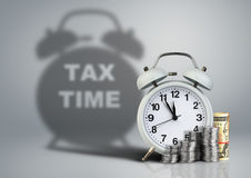 Wekker met geld en belastingstijdschaduw, financieel concept Stock Afbeelding