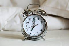 Wekker op bedbladen Stock Foto
