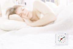 Wekker op de achtergrond van het slaapmeisje Royalty-vrije Stock Foto