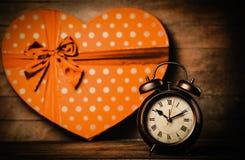 Wekker op de lijst met de gift van de hartvorm royalty-vrije stock foto's