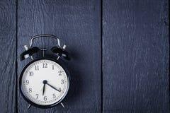 Wekker op een zwarte houten oppervlakte Stock Foto's