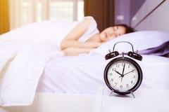 Wekker op lijst en vrouwenslaap op bed in slaapkamer stock afbeeldingen