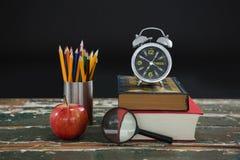 Wekker op stapel boeken met penhouder, appel, en vergrootglas Stock Afbeeldingen