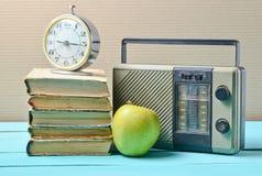 Wekker op stapel oude boeken, radioontvanger, appel op een blauwe houten lijst Retro stilleven stock foto