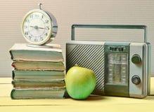 Wekker op stapel oude boeken, radioontvanger, appel op een blauwe houten lijst Retro stilleven stock foto's