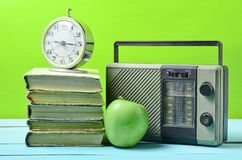 Wekker op stapel oude boeken, radioontvanger, appel op een gele achtergrond Retro stilleven stock afbeeldingen
