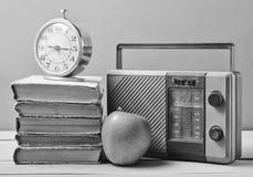 Wekker op stapel oude boeken, radioontvanger, appel op een roze achtergrond Retro stilleven royalty-vrije stock foto's