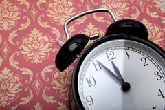 Wekker in retro stijl op uitstekende achtergrond Stock Fotografie