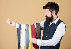 Welches bringt seine Kleidungsart zusammen Bärtiger Mann, der die rechte Krawatte für GeschäftsLebensstil wählt Gesch lizenzfreie stockbilder