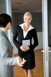 Welcome. Pretty female standing by door and communicating with colleague Stock Images