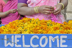 Welcome. Women with flowers in a market of India Stock Image