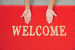Welcome. Hands With Welcome Sign And Red Color Mat Royalty Free Stock Photography