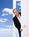 Welcome. Smiling gray-haired man opening a door Royalty Free Stock Photo