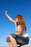 Welcome. A beautiful caucasian young woman sitting on a rock in front of blue sky background waving her hand for welcome Stock Image