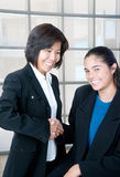 Welcome. Young businesswoman is hired by mature business woman in modern office space Stock Photos