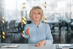 Welcome assured lady hand outstretched employment. Welcome team company. Assured senior business lady hand outstretched. Employment consultation partnership stock photo