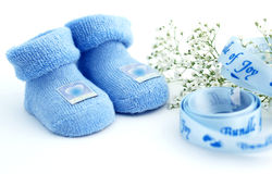 Welcome, baby boy!. Blue socks with blue ribbon and flower - macro Royalty Free Stock Images