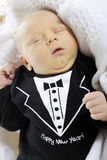 Welcome Baby New Year. Close-up of a sleeping newborn boy dressed in a black tux that welcomes the new year. On a white background royalty free stock photo
