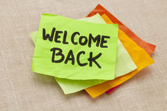 Welcome back. Handwriting on a green sticky note against canvas board